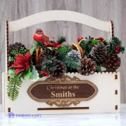 Christmas flower box with personalised embellishment and an arrangement of artificial festive flowers and read dried citrus fruit